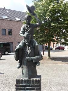 """beeld bij de kerk van Zichem: Ernest Claes met op zijn schouder """"de witte"""""""